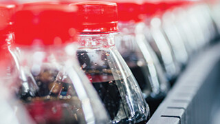 Soda pop bottles on a manufacturing line at a bottling plant where flexible manufacturing can improve efficiency.